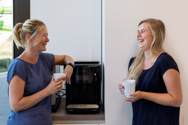 2 women talking by the coffee machine